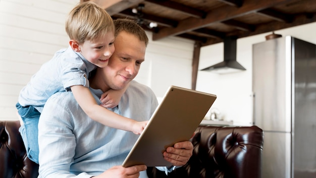 Medium shot father holding tablet
