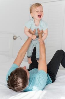Средний снимок отца, держащего малыша