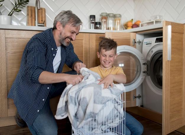 Padre e figlio a tiro medio che fanno il bucato