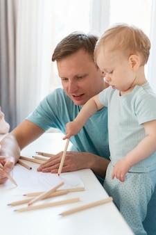 Medium shot father and kid drawing