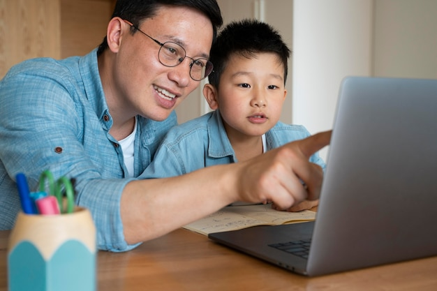 Medium shotfather and kid with laptop