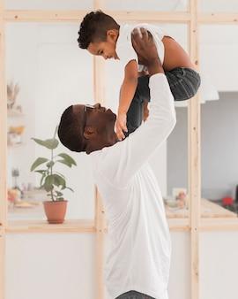 屋内で息子と遊ぶミディアムショットの父