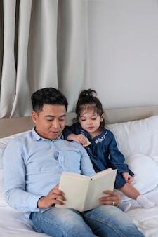 ミディアムショットの父親が女の子に読んでいる