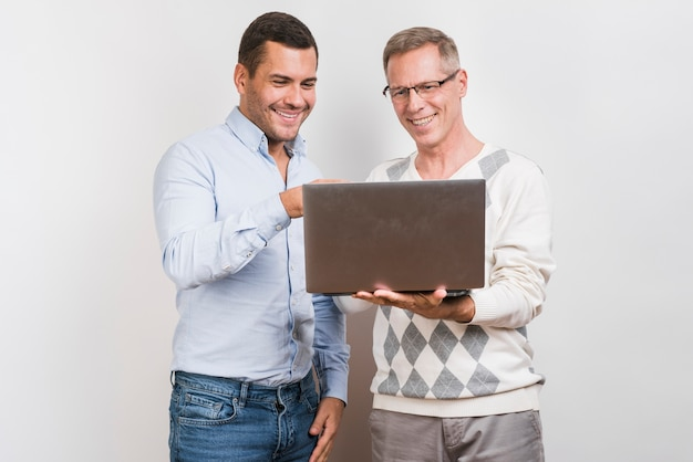 Medium shot of father and son with laptop