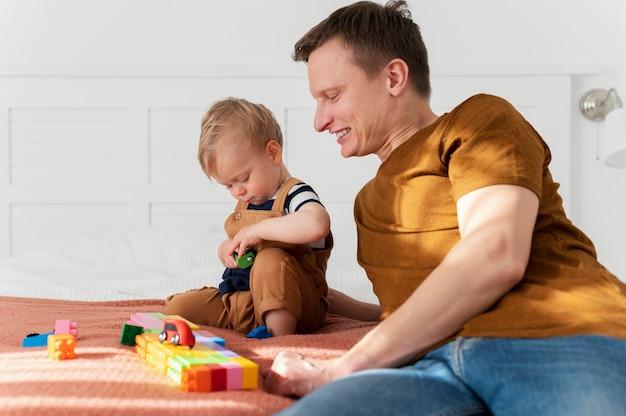 Отец среднего кадра наблюдает за игрой ребенка