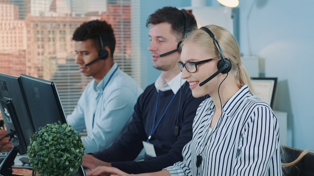 Medium shot of female customer service working in busy call center