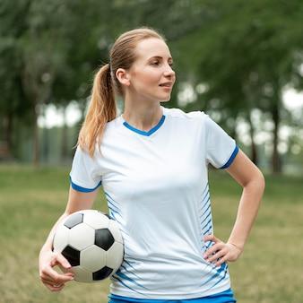 Средний выстрел женщина держит футбольный мяч