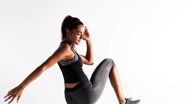 Medium shot fit girl in gym suit exercising indoors