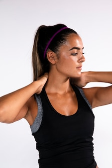Medium shot fit girl with hands on neck
