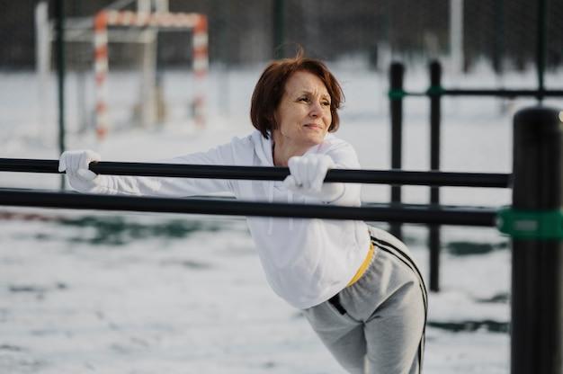Donna senior adatta del colpo medio all'aperto