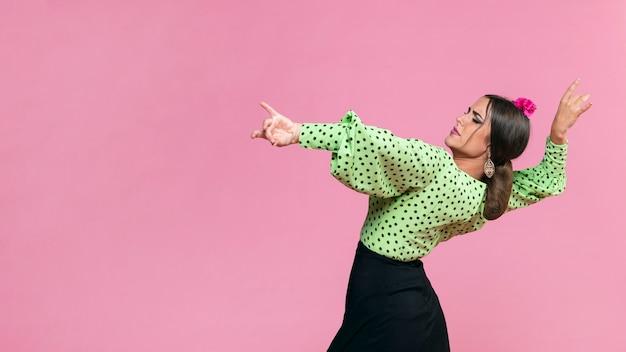 Medium shot flamenca performing floreo on pink background