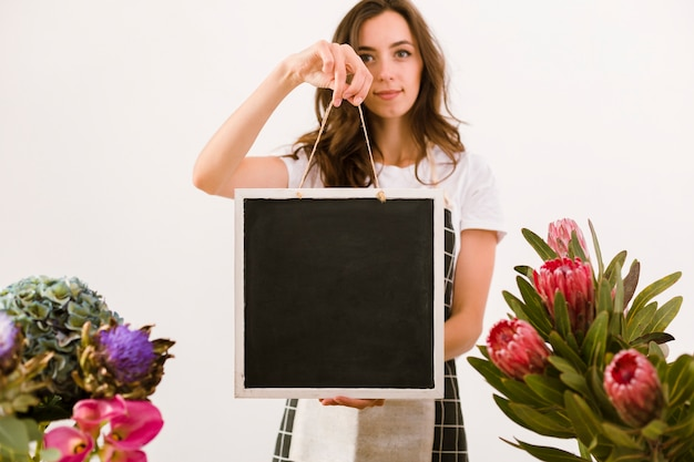 Medium shot florist holding a black board