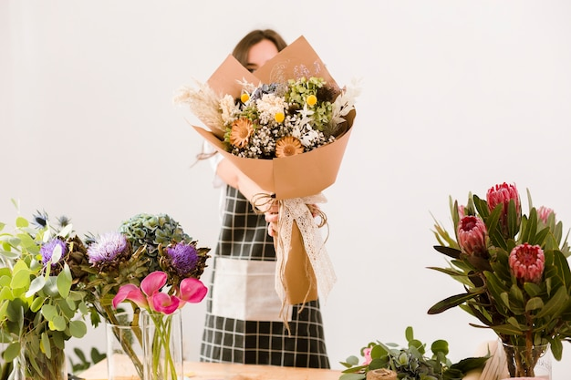 Medium shot florist holding up a beautiful bouquet