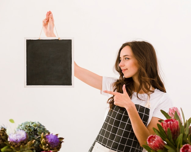 Medium shot florist pointing at a black board