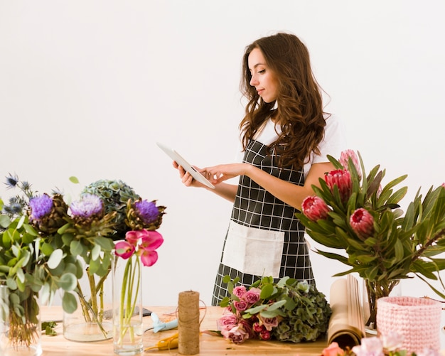 Medium shot florist with tablet and apron