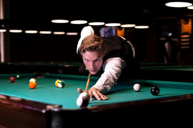 Medium shot focused man playing billiard