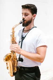 Medium shot focused musician playing the sax