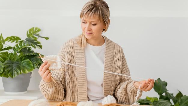 ミディアムショットに焦点を当てた女性の編み物