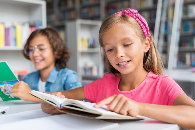 Друзья среднего размера вместе делают домашнее задание в библиотеке