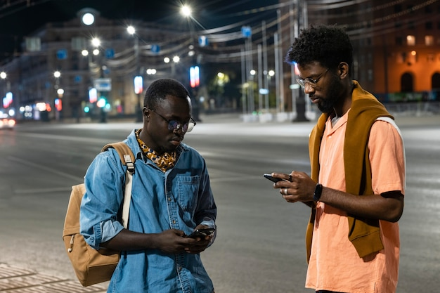 Medium shot friends holding phones