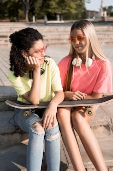 Medium shot friends holding skateboard