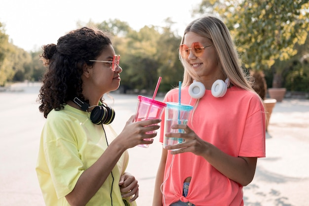 Medium shot friends holding water cups