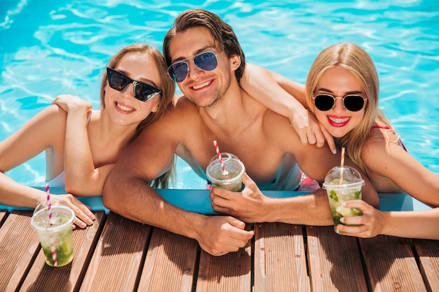 Medium shot friends looking at camera in swimming pool