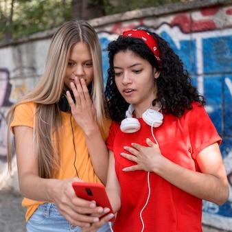 Medium shot friends looking at phone