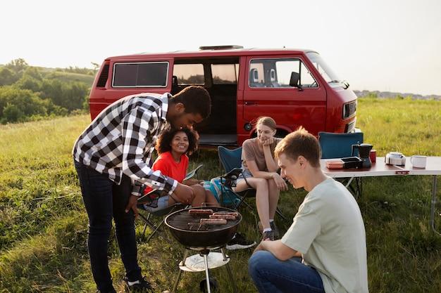 Amici di tiro medio che fanno barbecue in natura
