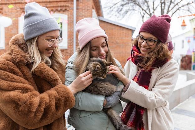 ミディアムショットの友達が猫をかわいがる
