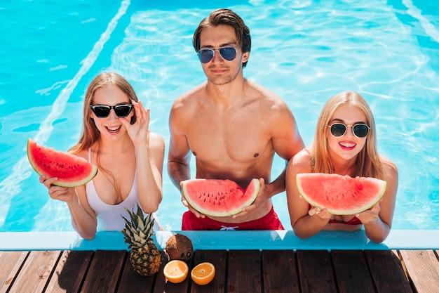 Medium shot friends posing with watermelon