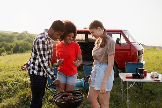 Amici di tiro medio che preparano il barbecue