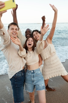 해변에서 셀카를 찍는 미디엄 샷 친구들