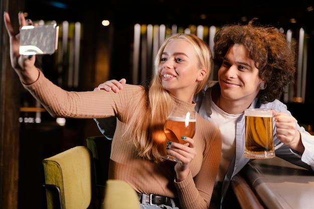 Amici di tiro medio che prendono selfie al pub