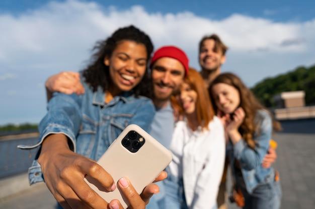 Medium shot friends taking selfie together