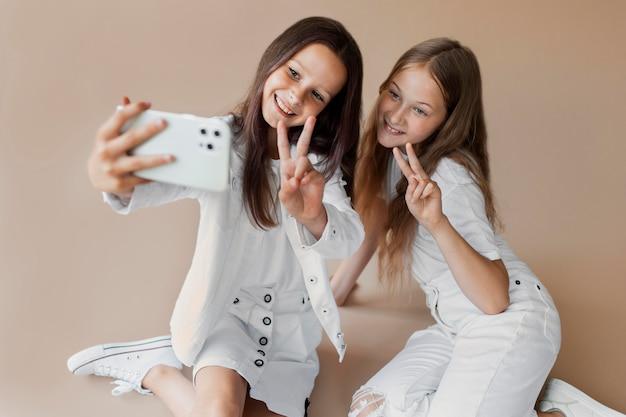 Друзья со средним снимком, делающие селфи