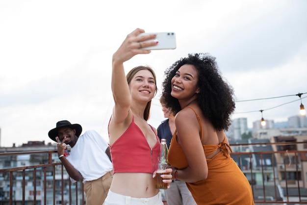 自撮り写真を撮るミディアムショットの友達