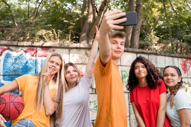 Medium shot friends taking selfies