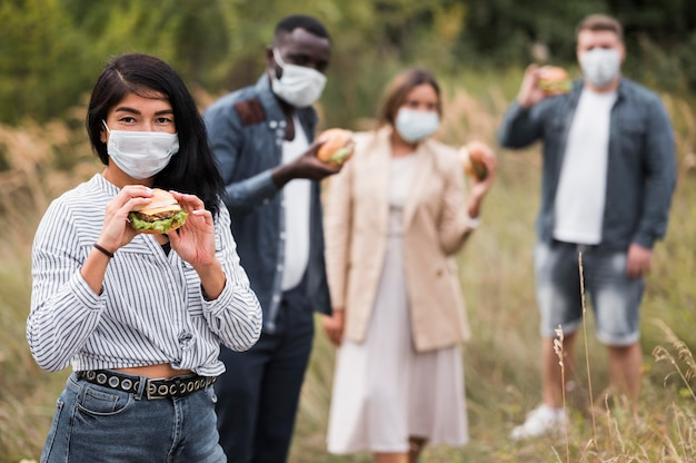 Друзья среднего размера с гамбургерами на свежем воздухе