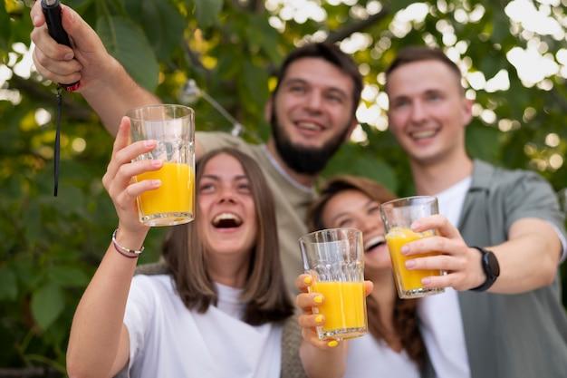 Друзья среднего размера с стаканами для сока