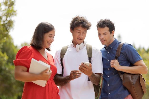 Medium shot friends with phone