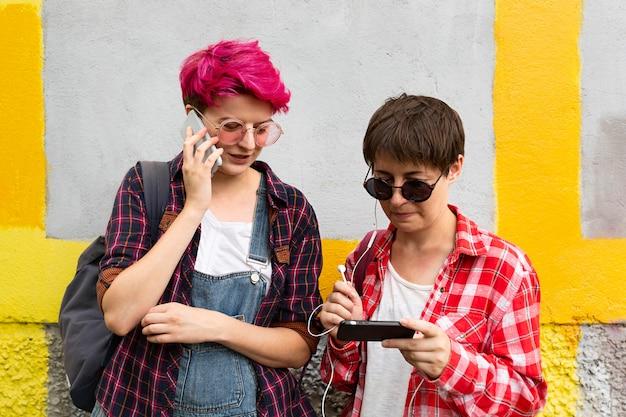 Medium shot friends with smartphones