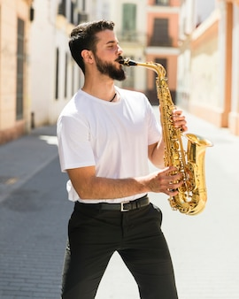 Medium shot front view musician playing saxophone in street