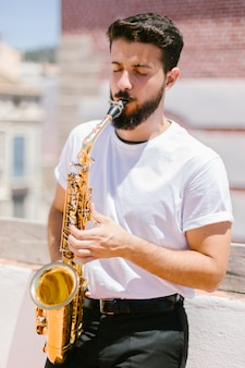 Средний выстрел музыкант вид спереди играет на саксофоне
