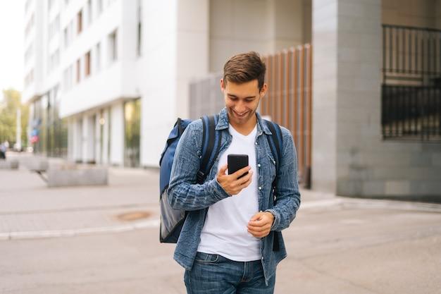 도시 거리에 서 있는 전화에서 탐색 앱을 사용하여 열 배낭을 메고 쾌활한 잘 생긴 남성 택배의 중간 샷 전면 보기. 스마트폰을 찾고 클라이언트 주소를 검색하는 배달 남자.