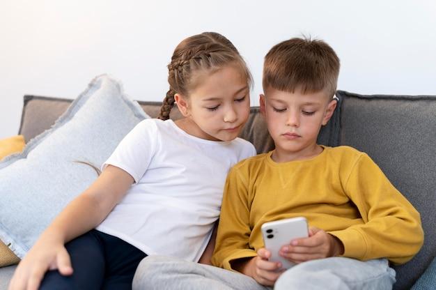 Средний снимок девочка и мальчик с телефоном