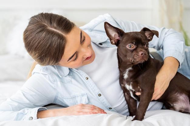Девушка среднего кадра и собака в постели