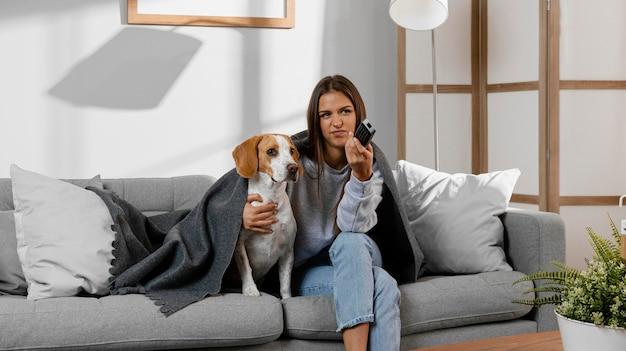 Девушка среднего кадра и собака смотрят телевизор