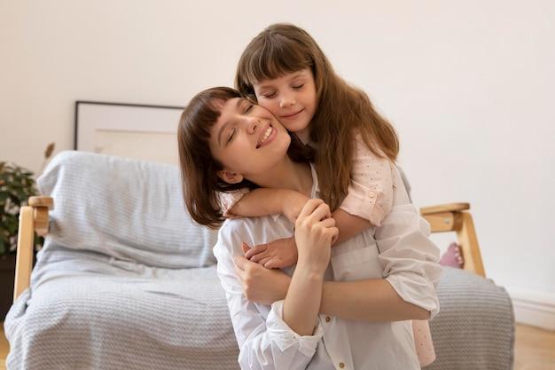 ミディアムショットの女の子と母親が抱き締める
