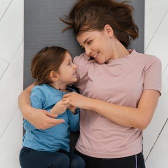 ミディアムショットの女の子とマットの上の母親